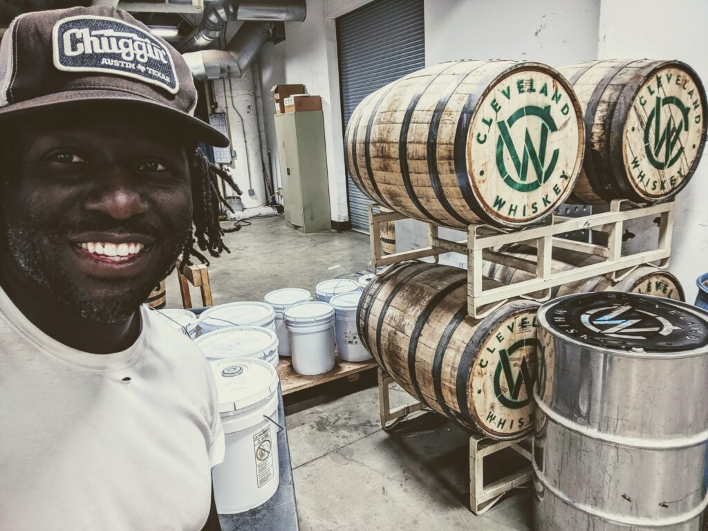 Photo of man with Cleveland Whiskey barrels.